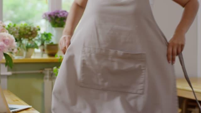 vídeos de stock e filmes b-roll de florist putting on apron before opening - avental