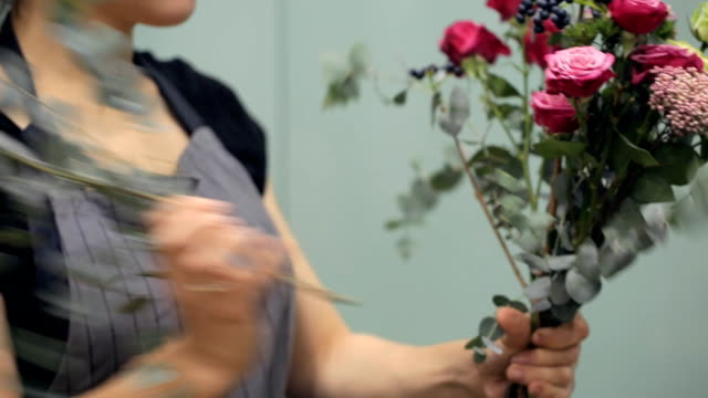 Florist recruit bunch of flower to create composition inside video