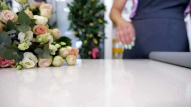 Florist rolls a paper on the table to wrap bouquet of roses, closeup view.