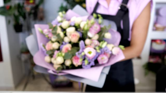 Florist shows beautiful bouquet of roses, gypsophila and leaves in purple paper.