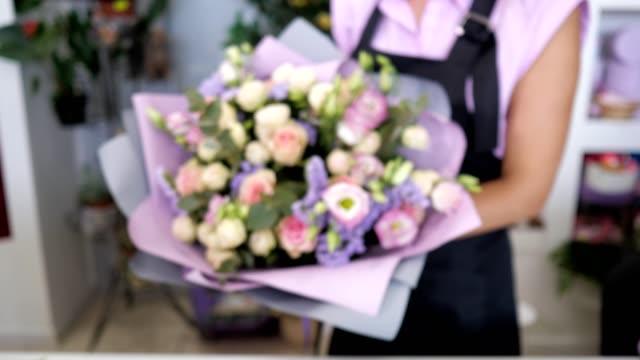 vidéos et rushes de le fleuriste montre beau bouquet de roses, de gypsophile et de feuilles en papier violet. - composition florale