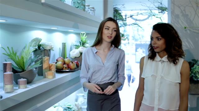 Florist shows design compositions to her client at flower shop video