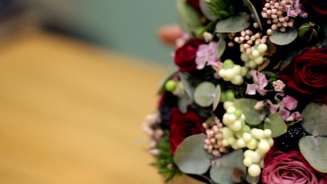 Florist shows finished flower arrangement on table inside office video