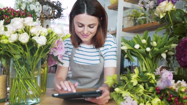 vídeos de stock, filmes e b-roll de florista usando um tablet digital. - comércio eletrônico