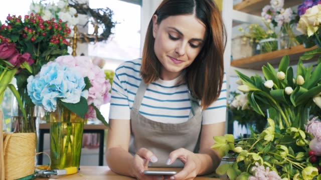 Florist using her smart phone. Florist using her smart phone to communicate with someone or surfing the net. owner stock videos & royalty-free footage