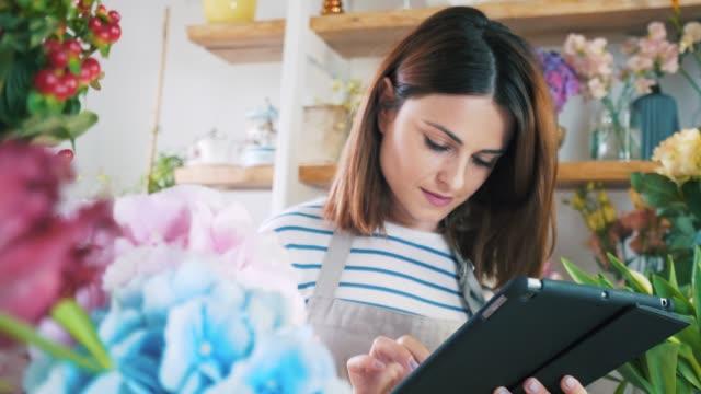 florist med surfplatta. - blomstermarknad bildbanksvideor och videomaterial från bakom kulisserna