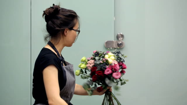 Florist with all concentration collects flowers in bouquet video