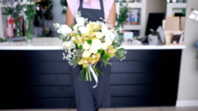 vidéos et rushes de la femme de fleuriste vient avec le beau bouquet des roses et des lis dans ses mains. - bouquet formel