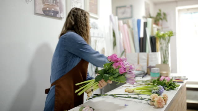 vídeos de stock e filmes b-roll de florist woman make a flowers bouquet - trabalho de design