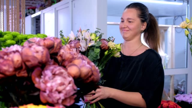 Florist woman makes big flower bouquet and talks with client in flower shop. video