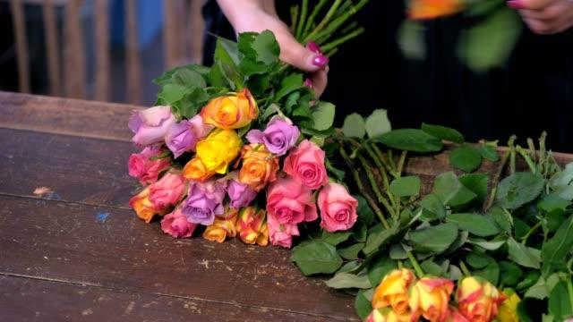 vidéos et rushes de la femme de fleuriste fait le bouquet de petites roses colorées dans la boutique, plan rapproché de mains. - composition florale