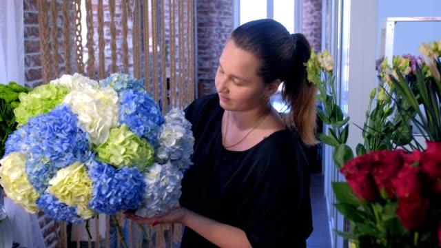 stockvideo's en b-roll-footage met de vrouw die van de bloemist met reusachtig mooi boeket van hortensiabloemen in winkel stelt. - hortensia