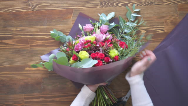 Florist wrapping bouquet in pack paper