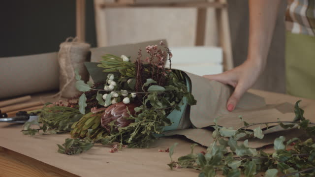 vidéos et rushes de fleuriste bouquet de fleurs en papier kraft d'emballage - composition florale