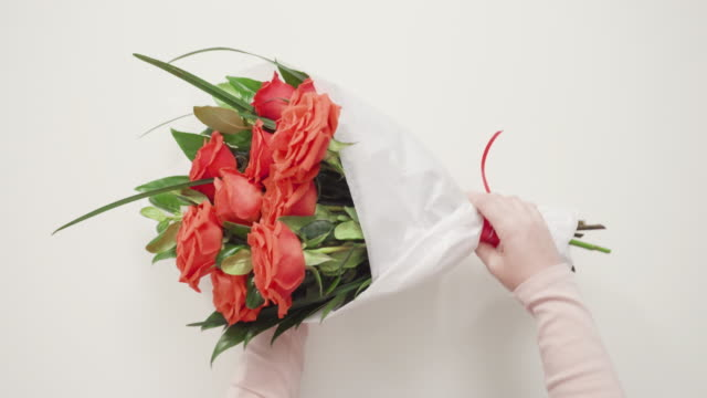 florist wrapping red roses into a beautiful bouquet. - bouquet video stock e b–roll