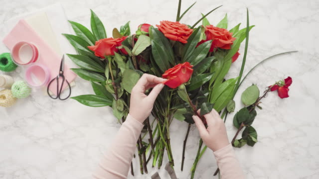 Florist wrapping red roses into a beautiful bouquet.