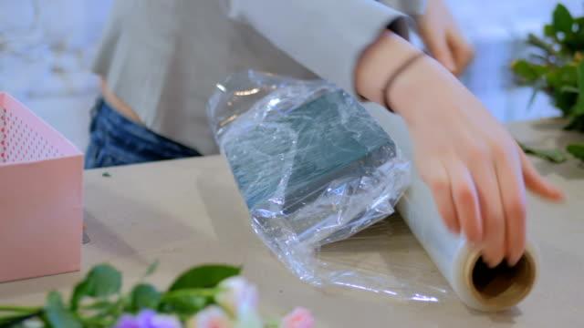 Floreria envuelve la espuma floral en film transparente para arreglo de flores en floristeria - vídeo