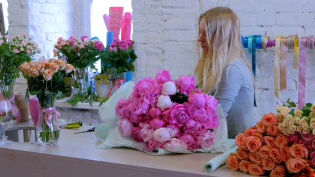 Florist wraps flowers in gift paper at flower shop Professional woman floral artist, florist wraps flowers - pink peonies in gift paper at workshop, flower shop. Close up shot. Floristry, handmade and small business concept wrapped stock videos & royalty-free footage