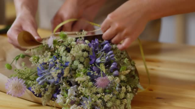 florists wrapping exquisite wildflower bouquet together - bouquet video stock e b–roll