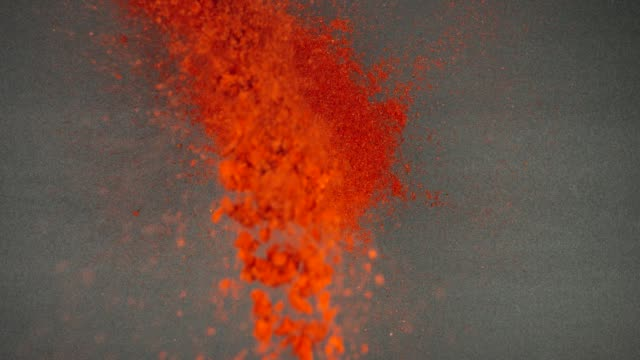 TOP VIEW: Flow of red pepper falls on a black table - Slow Motion TOP VIEW: Flow of red pepper falls on a black table - Slow Motion spice stock videos & royalty-free footage