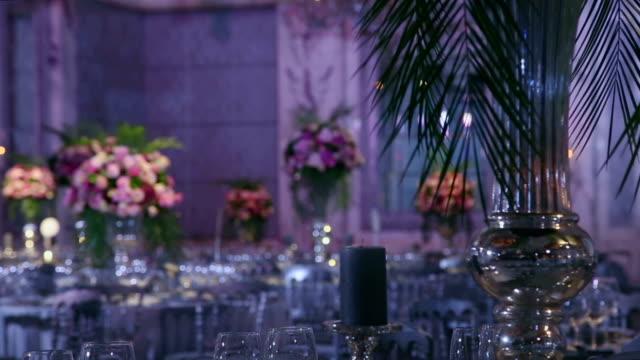Flower arrangement for an indoor ballroom wedding table decoration video