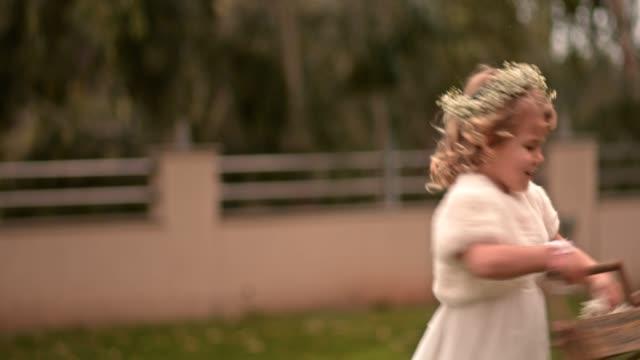 stockvideo's en b-roll-footage met bloemenmeisje spinnen en gooien bloemblaadjes op trouwdag - blond curly hair