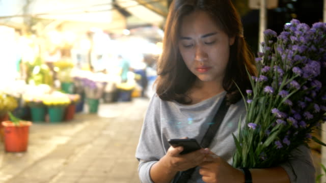 花市場: 女性の夜のスマート フォンを使用して - 花市場点の映像素材/bロール