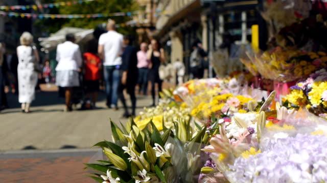 flowers and city centre shoppers. - blomstermarknad bildbanksvideor och videomaterial från bakom kulisserna