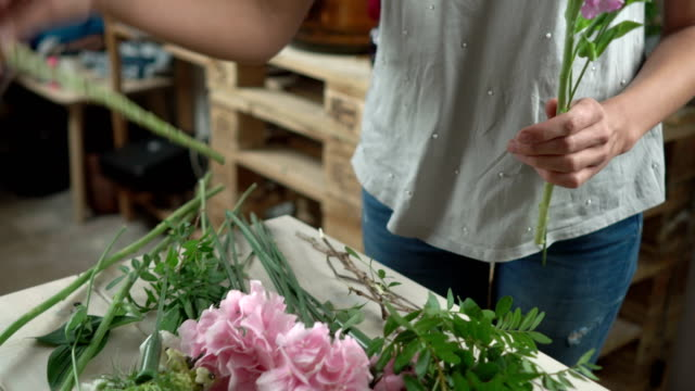 flowers are spread out on a wooden counter of a flower shop, the florist takes the flower from the counter and begins to make a bouquet close-up 4k. - grand opening stock videos and b-roll footage