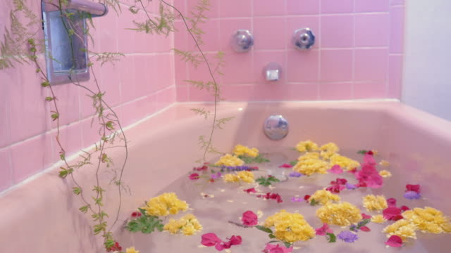 Flowers Float on the Surface of a Pink Bathtub in a Luxury Spa