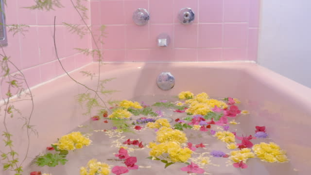 Flowers Floating on the Surface of a Pink Bathtub