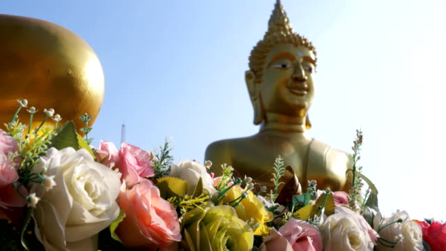 Flowers on a background of a large golden Buddha in the temple of Thailand. Pattaya Flowers on a background of a large golden Buddha in the temple of Thailand. Pattaya. Wat Phra Yai Temple Or Big Buddha Statue. pattaya stock videos & royalty-free footage