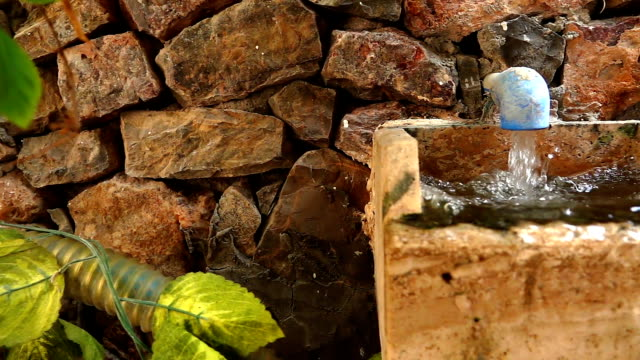 Flowing Water in Fountain and Stone Brick Wall