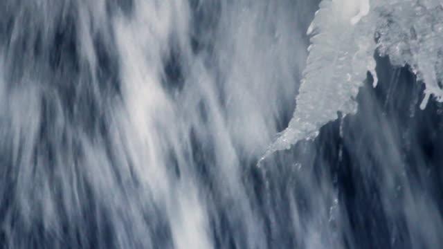 Flowing water of mountain waterfall in winter. Winter waterfall. Ice waterfall video