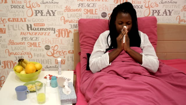 Flu infection is here!Flu season. Sick woman covered with a blanket lying in bed with high fever and a flu. video