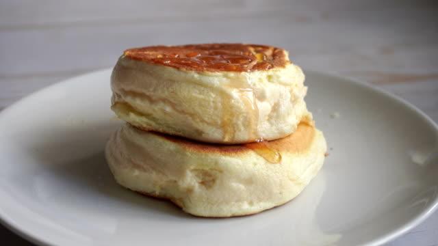 ふわふわのスフレパンケーキは、シロップを注ぐ白いプレートの上に積み重ねる - ふわふわ点の映像素材/bロール