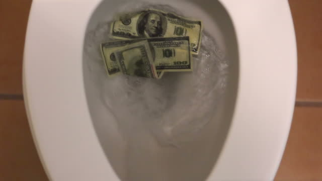 Flushing dollars in toilet bowl in slow motion 250fps video