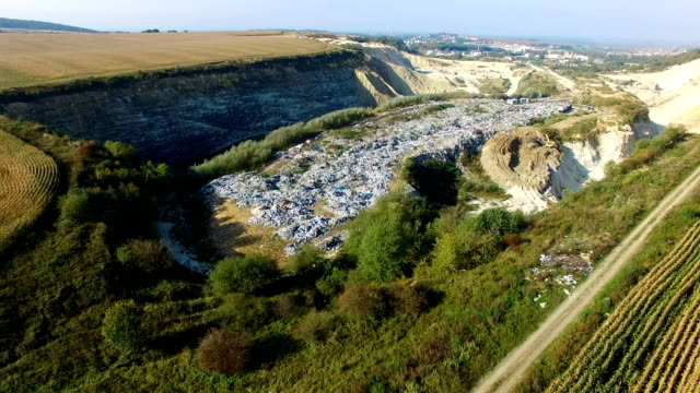 Fly around rubbish dump near weat agricultural fields. Aerial view video