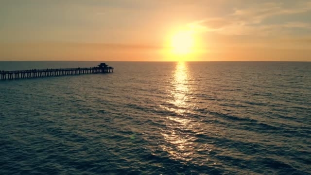 Fly back aerial shot of silhouette of fishing pier video