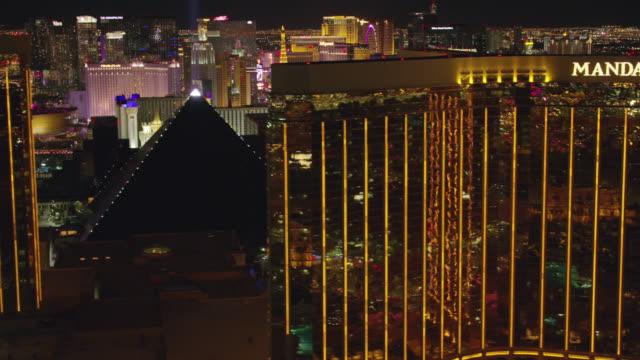 fly by mandalay bay hotel and casino revealing las vegas strip at night. - las vegas video stock e b–roll