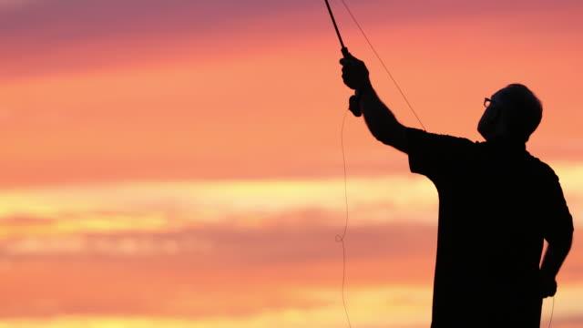 Fly Fishing Fisherman Silhouette on Lake at Sunset video