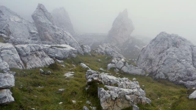 vidéos et rushes de volez dans le brouillard au-dessus des roches - paysage extrême