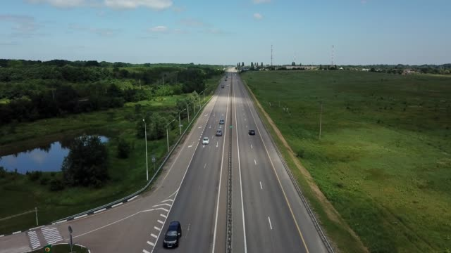fly over highway road junction in the countryside with trees and cultivated fields. - autobahn video stock e b–roll