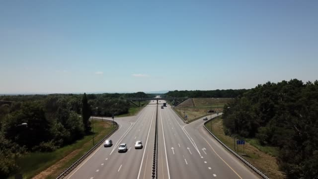 Fly over highway road junction in the countryside with trees and cultivated fields. Cloverleaf interchange seen from above. autobahn stock videos & royalty-free footage
