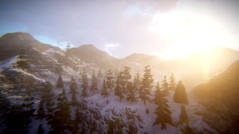 Fly over mountains Camera flying over mountains. Volumetric light / God rays. Sunset sky with sun and moving clouds. Aerial view. extreme terrain stock videos & royalty-free footage