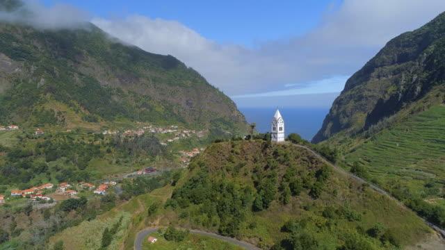 vídeos de stock e filmes b-roll de fly past a church on a hill in madeira - funchal madeira