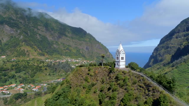 Fly Past an Old Chapel Tower on a Hill in Madeira Madeira is a small Portuguese island, situated North of the Canary Isles in the Atlantic Ocean. The island boasts incredible scenery due to the volcanic landscape which creates vast and steep mountains across the 20 mile island. funchal stock videos & royalty-free footage