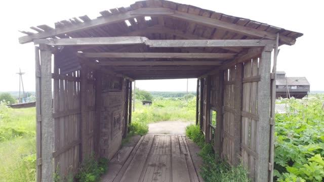 荒涼とした村の道の上にトラフの入り口古い小屋を飛ぶ ビデオ