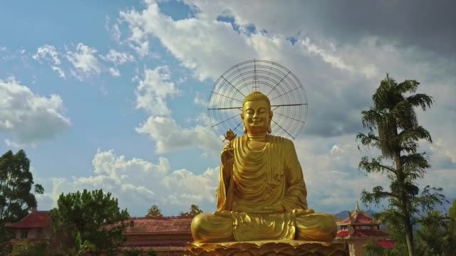 Flycam Approaches to Golden Buddha against Blue Sky