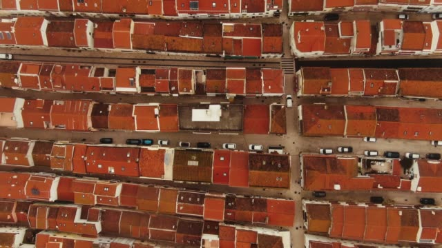 flycam rises over terracotta roofs houses and parked cars - vídeo